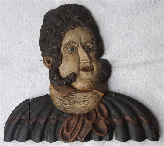AN EARLY 19TH CENTURY CARVED AND POLYCHROME PAINTED HEAD DEPICTING GEORGE III, wearing a ruff, long sideboards and well styled hair, the face and overall piece with original paintwork, 34 cm high x 31cm wide