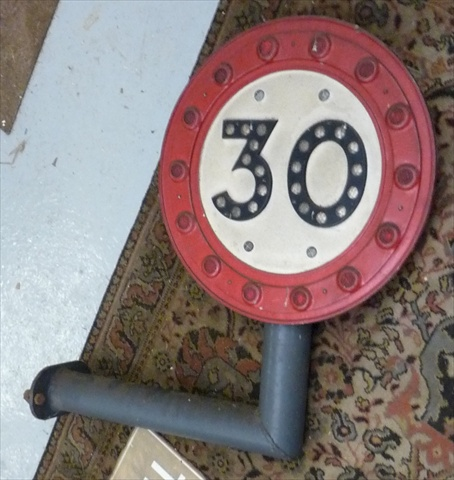 A MID 20TH CENTURY 30 (MPH) STREET SIGN, the black letters with white reflectors on a white ground within a circle of red with reflectors, 47cm diameter on original tubular steel right angle bracket arm with bolt fittings