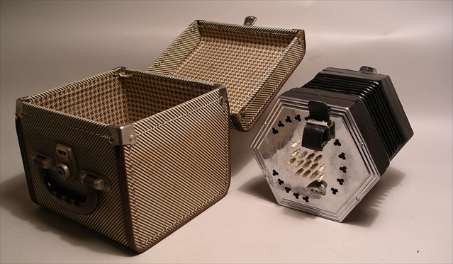 AN EARLY 20TH CENTURY EMPIRE BRITISH MADE CONCERTINA THE MAYFAIRE with black leather bellows, in original checker luggage case