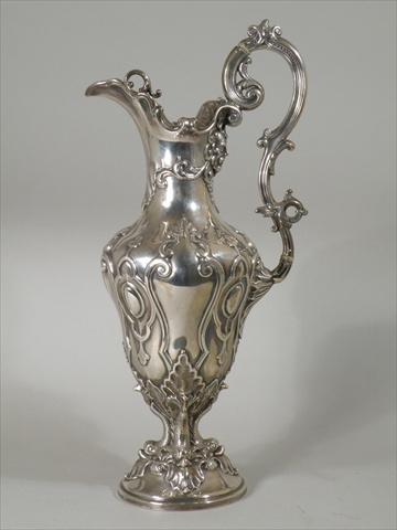 HAWKESWORTH EYRE & Co. A VICTORIAN SILVER CLARET JUG having scroll handle and leaf lid on a richly repousse worked urn shape body with mask and scrolls, raised on four-way dolphin pedestal with circular foot, Sheffield 1853, 1000g