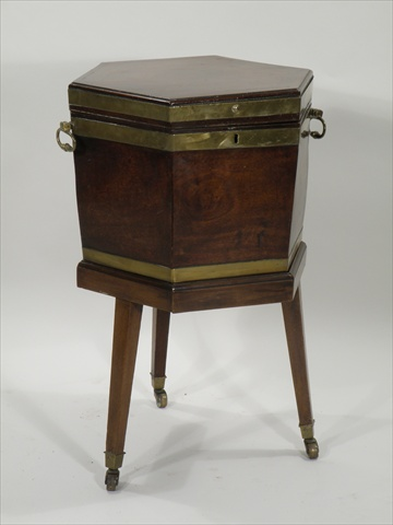 A GEORGE III MAHOGANY CELLARET having octagonal top with triple brass bound surround, later zinc liner mounted on period stand with square tapered legs and brass cup castor terminals