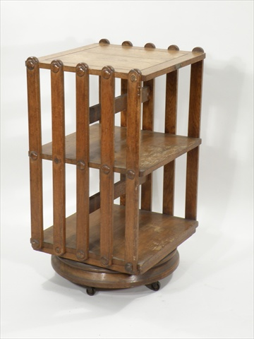 A LATE 19TH CENTURY AMERICAN PATENTED OAK REVOLVING BOOKCASE having three tiers, slatted sides and circular moulded base with castors, bear label Patented in USA Jan 23rd 1883, 1m high x 42cm wide