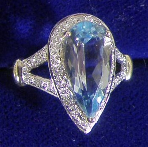 A 9CT GOLD DRESS RING set with pear drop cut blue topaz with small diamond surround (ref. 6)