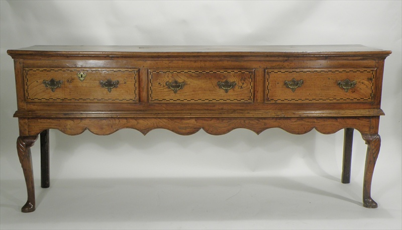 A MID GEORGIAN OAK AND ELM DRESSER BASE (with later alterations) having figured plank top over three inline drawers with later Puginesque inlay mounted on twin later cabriole forelegs with anthemion carved knees and pad feet, 85cm high x 1.88m wide