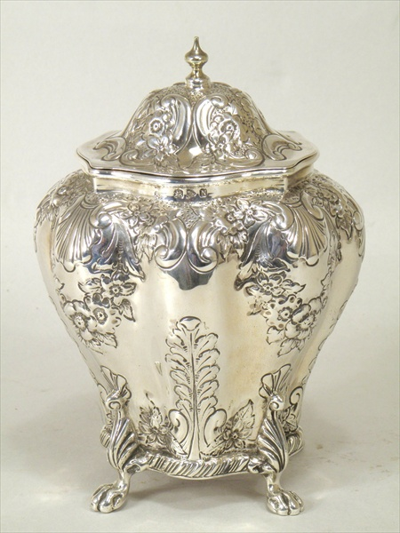 NATHAN & HAYES A VICTORIAN SILVER TEA CADDY, having hinged lid upon a lobed body with allover period repousse garlands, scallops and scrolls, raised on four lion paw feet, Chester 1896, 250g.