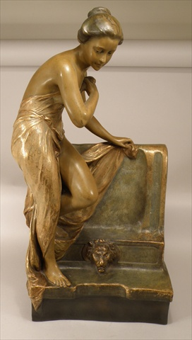 E**TELL AN EARLY 20TH CENTURY GOLDSCHEIDER EARTHENWARE CENTREPIECE moulded as a young lady in bathing robe, resting with her foot on a stone fountain with a lion mask below, allover brown and sea green colouring highlighted with gilt, bears Goldscheider backstamp, incised signature, date code for 1904, 69cm high Illustrated Front Cover