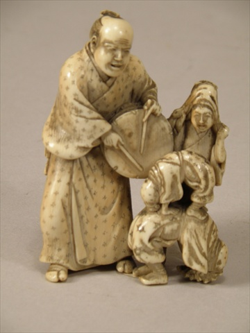 A MEIJI PERIOD JAPANESE CARVED IVORY GROUP OF ACROBATS, a man with a tambourine and three children, signed, 8cm high