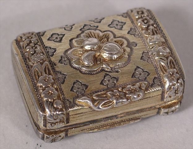 A REGENCY SILVER PARTIAL GILT VINAIGRETTE having luggage style exterior with  twin floral applied bands and various worked geometric decoration, hinged opening to reveal a floral gilt grille interior, Birmingham 1818