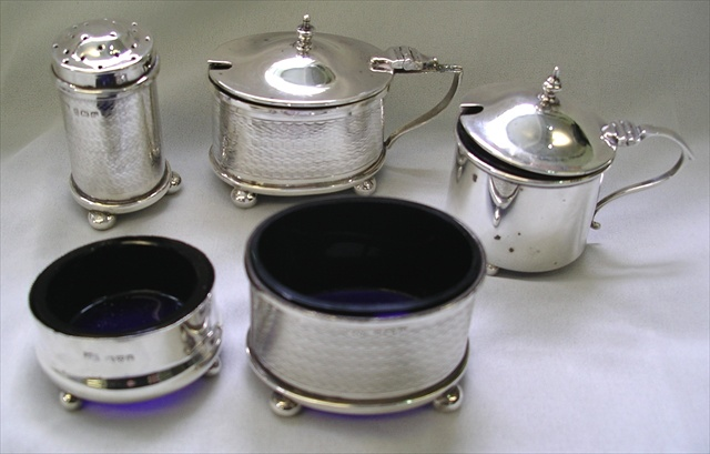 A THREE-PIECE SILVER CONDIMENT with engine turned decoration, ANOTHER SALT AND MUSTARD dissimilar, mixed dates