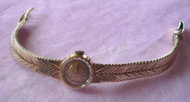 AN 18CT GOLD GIRARD PERREGAUX LADYS COCKTAIL WATCH having plain case with facetted inset glass over a champagne coloured dial with batons, mechanical mechanism with lever escapement, on original diamond cut multi chevron design flexible bracelet