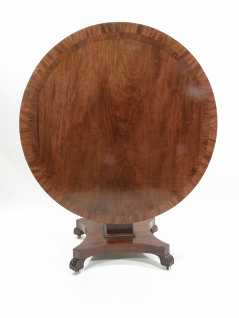 A MID VICTORIAN MAHOGANY BREAKFAST TABLE having crossbanded and figured top, squared and stepped column with moulding, mounted on a re-entrant quatrefoil base with possibly late moulded shaped feet, 73cm high x 118cm diameter