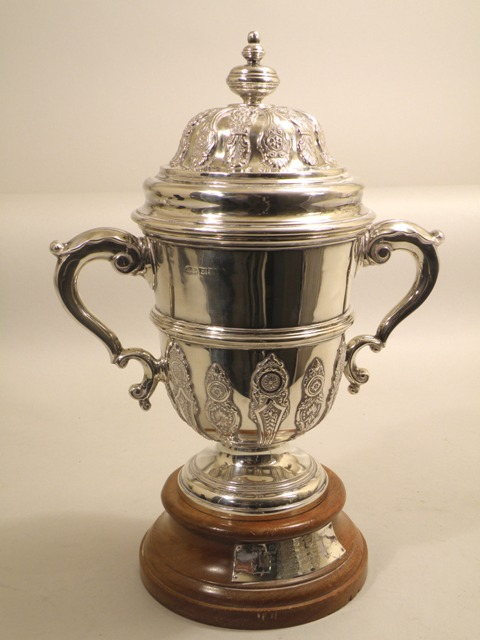 DEAKIN & FRANCIS A REGENCY STYLE SILVER TROPHY CUP having dome lid with knop finial and cast and applied rosette scroll and palmette motifs, gilded interior, twin flank scroll handles, repeated decorated lower belly and turned pedestal foot, and wooden plinth, Birmingham, date obscured, probably circa 1890, 1500g, 30cm high