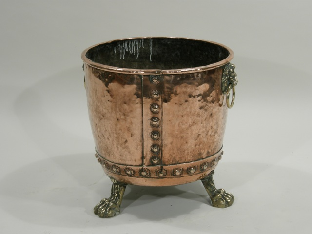 A 19TH CENTURY COPPER LOG BIN of cylindrical form with lion ring mask handles supported on three paw feet, 48cm x 46cm