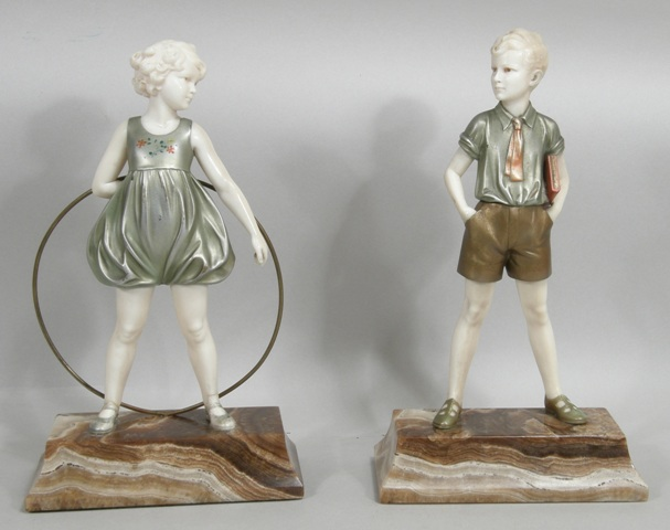 FERDINAND PREISS A PAIR OF BRONZE AND IVORY FIGURINES Sonny Boy, standing square with book under his arm and Hoop Girl, with flowing dress, each on matching brown onyx plinth, 21cm high