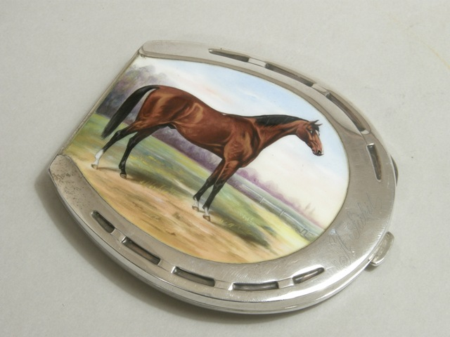 A CONTINENTAL SILVER COLOURED METAL AND ENAMELLED CIGARETTE CASE fashioned as a horseshoe, the front enamelled with a chestnut stallion in a landscape, engraved A. Sabit, with gilded interior