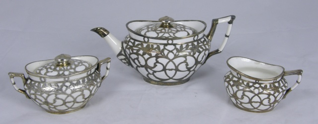 A VICTORIAN MINTONS SILVER OVERLAID WHITE PORCELAIN THREE PIECE TEA SET, each of oval form with all over floral tracery, bears red mark, England