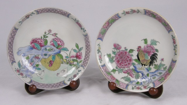 A PAIR OF PROBABLY QIANLONG PERIOD RUBY BACKED EGG SHELL SAUCERS painted in famille rose enamels showing chickens amongst foliage, 20cm diameter (with wooden display stands)
