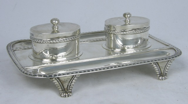 CARRINGTON & CO. A SILVER DESK STAND having twin oval lidded wells with clear glass reservoirs bolted to the tray base with applied gadroon border, twin pen channels, raised on four tapered feet, London 1909