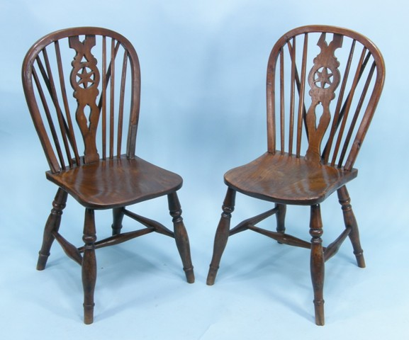 A SET OF SIX VICTORIAN YEW, ASH AND ELM WINDSOR CHAIRS, each having wheel and stick back, sculptured seat, raised on turned legs united by an 'H' frame stretcher