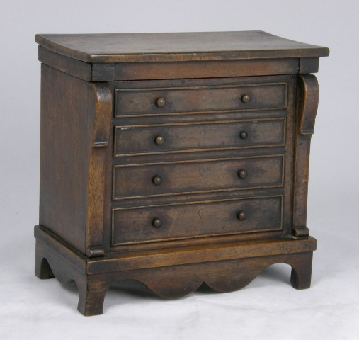 A MAHOGANY MONEY BOX FASHIONED AS A 19TH CENTURY CONTINENTAL CHEST having a hinged top opening to reveal two coin slots over four facsimile drawer fronts, raised on a bracket plinth, 21cm high x 22cm wide