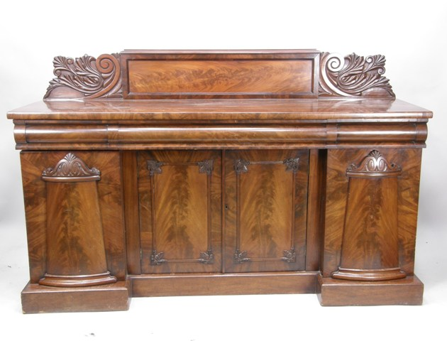 A VICTORIAN MAHOGANY SIDEBOARD having an upstand figure veneered and acanthus carved flat plank top with assorted cushion fronted drawers under, twin central cupboard doors flanked by twin bow front figured doors, raised on inverted plinth, 111cm x 183cm
