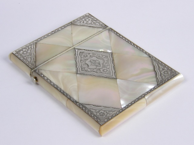 A VICTORIAN SILVER MOUNTED AND MOTHER-OF-PEARL VISITING CARD CASE, the front tooled with central lozenge and spandrels bright cut floral worked, interset with mother-of-pearl lozenges and an entirely mother-of-pearl lozenge back, 105mm x  80mm