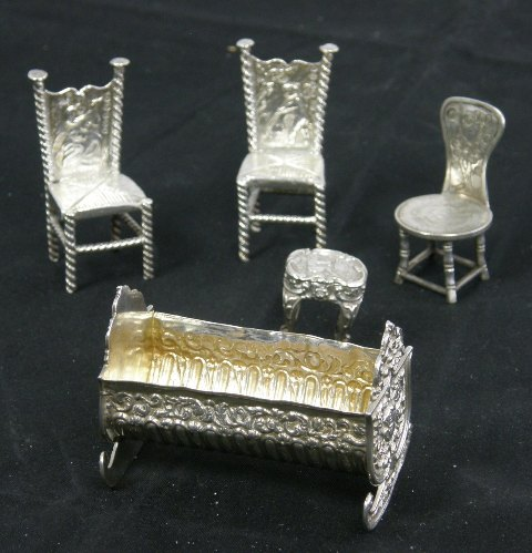 A SELECTION OF SILVER MINIATURE FURNITURE comprising; a press decorated cradle, Birmingham 1896, a pair of foreign silver coloured metal chairs, another chair and a stool  on cabriole legs