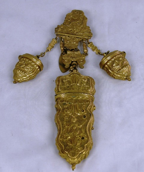 A GILT METAL CHATELAINE, the clip decorated with a Bacchanalian figure and an etui below fitted with one original knife and two little boxes