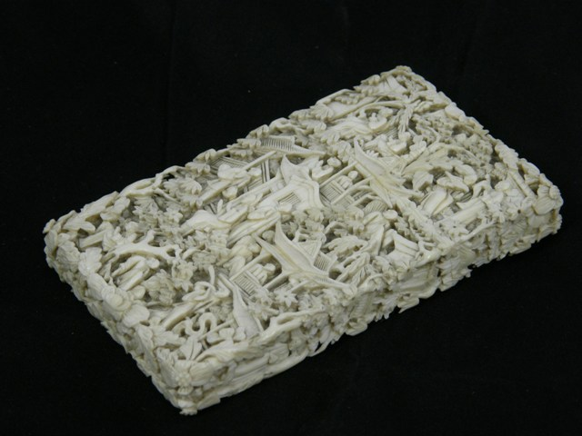 A LATE 19TH/EARLY 20TH CENTURY JAPANESE CARVED IVORY VISITING CARD CASE decorated with figures, buildings, trees, flowers and foliage, 11cm high x 65mm wide