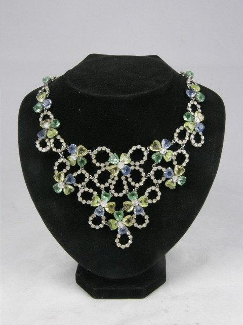 CHRISTIAN DIOR A MULTI-COLOURED PASTE NECKLET comprising multiple florets of yellow, green and blue stones, bordered by white stones in a chromed setting