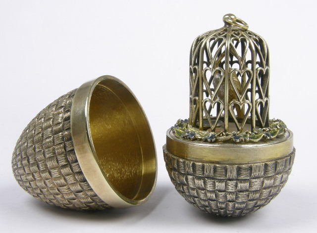 STUART DEVLIN A SILVER GILT NOVELTY EGG having all over textured exterior, the interior fashioned with a wirework bird cage and two parrots on a branch, Numbered 271, in original fitted box
