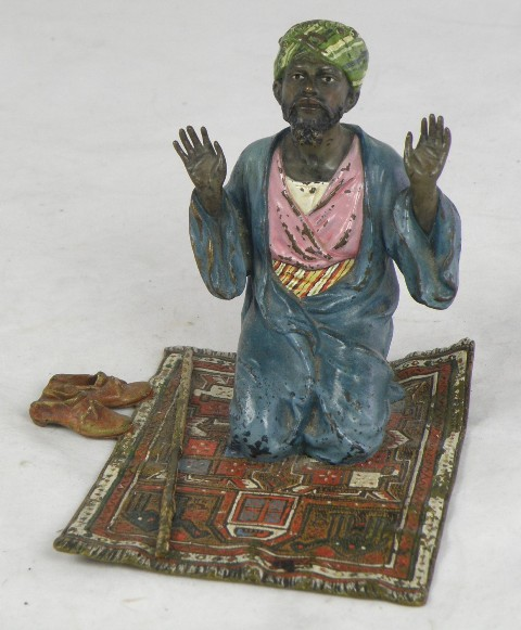 FRANZ BERGMANN A LATE 19TH /EARLY 20TH CENTURY AUSTRIAN CAST BRONZE MODEL OF AN ARABIC GENTLEMAN seated on his prayer rug with stick and slippers beside, kneeling to Allah, unmarked, 15cm x 15cm