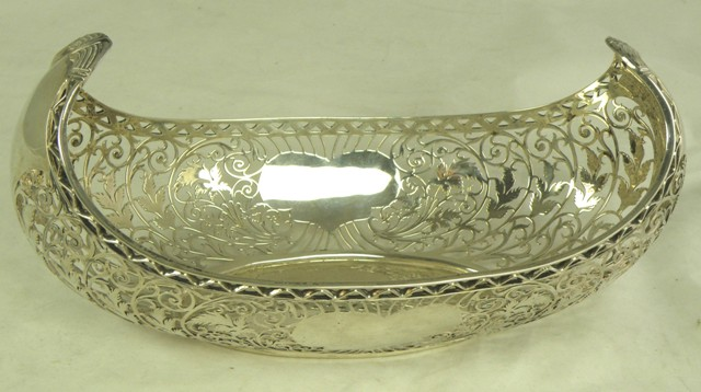 JAMES DIXON & SONS A SILVER FRUIT BOWL fashioned loosely as a Viking boat, oval with upswept ends, richly foliate and scroll fretted sides with heart shape cartouches, Sheffield 1929, 779g