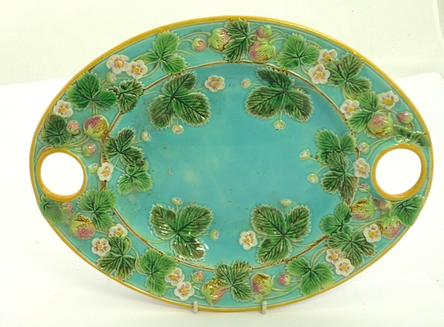 IN THE MANNER OF GEORGE JONES A VICTORIAN MAJOLICA STRAWBERRY OVAL SERVING PLATTER, with twin integral circular loop handles, all over relief moulded fruit and leaf decoration, bears a Victorian Patent Office registration mark verso for February 1st 1872, 30cm x 39cm