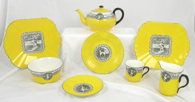 A SHELLEY CHINA TEA SET having vivid yellow ground and black transfer centre with dancing maidens, comprising teapot, sugar, milk, six cups, saucers, tea plates and two bread and butter plates