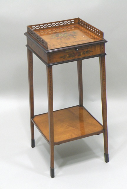 AN EARLY 20TH CENTURY SHERATON REVIVAL SATINWOOD NIGHT/BEDSIDE TABLE, having fretted gallery top, Chamberstick slide, painted floral decoration, raised on four squared legs united by a square stretcher, 70cm x 31cm