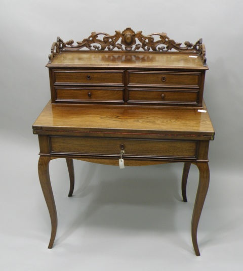 A LATE VICTORIAN PROBABLY COLONIAL ROSEWOOD BUREAU DE DAME having a superstructure with four drawers and fretted carved decoration, fold-open writing slope with modern skiver and frieze drawer below, raised on four French cabriole forelegs, 1m high x 78cm wide