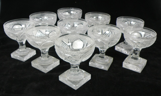 A SUITE OF LATE 19TH/EARLY 20TH CENTURY POSSIBLY FRENCH LEAD CRYSTAL GLASSES each profusely decorated with hob nail cutting and mounted on a square pedestal base, comprising ten champagne, eight large goblets, seven smaller goblets and eight large sherry, and TWO DECANTERS with flattened stoppers, total 33 glasses and 2 decanters and stoppers (ref box16 & 20)