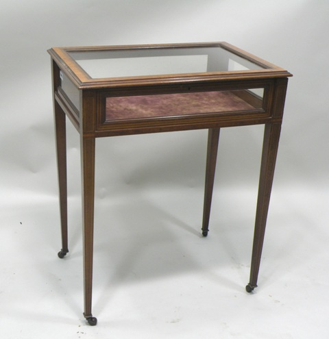 AN EDWARDIAN MAHOGANY, BOX WOOD INLAID AND SATINWOOD CROSSBANDED DISPLAY TABLE having hinged top with moulded surround and plain glass insets, four glass surround, raised on four squared tapered legs with brass castor terminals, 74.5cm x 59.5cm (refLT53)