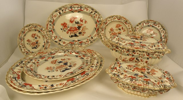 A VICTORIAN COPELAND EARTHENWARE DINNER SERVICE decorated in the English Imari palette, highlighted with gilt, comprising, a large tureen and cover, 21cm x 40cm, three smaller 14cm x 30cm including lids, twenty-five 26cm diameter plates, twenty-three bowls 26cm diameter, a meat platter 53cm x 40cm, three graduated platters 47cm, 43cm and 37cm wide, two oval dishes 23cm wide, and nine plates 23cm diameter