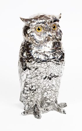A large continental silver owl cigarette holder, Berthold Muller, import mark for London 1927, naturalistically modelled as an owl with glass set eyes, the head with hinged opening to reveal interior compartment, 28cm high, weight 45.2oz  (Provenance- purchased 30th March 1983 from N. Bloom & Son) illustrated