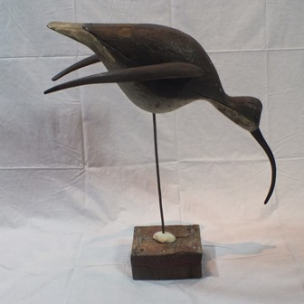 GUY TAPLIN (b.1939) Winged Curlew a carved and painted driftwood sculpture mounted on metal rod, with sea shell and block base, 45cm wide, 56cm high, 24cm deep.  (Provenance - Messums, Cork Street, London. Exhibition of Guy Taplins work, 2013) illustrated