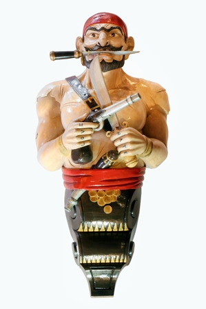 A 20th century carved wood and painted ships figure head in the form of a Pirate wearing a red bandana, a dagger between his teeth, a knife and pistol in his hands, Love and Hate painted to his knuckles, brown painted scroll base (hand carved in Bali), 1.30m high illustrated