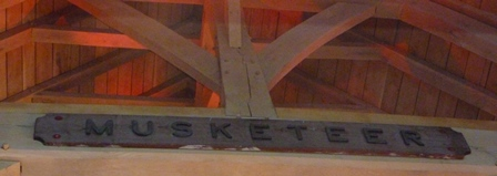 A maritime name plate, Musketeer oak board mounted with cast metal letters, with evidence of them having been painted/gilded, 2.13m wide, 27cm high, letters 13cm high