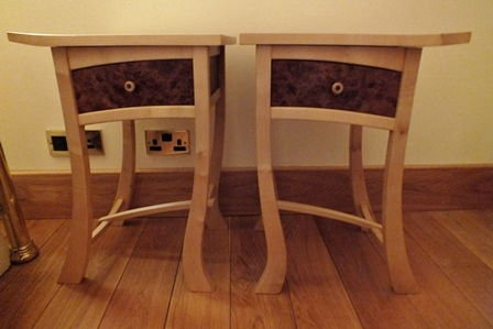 A pair of Cadman Fibonacci dancing furniture wavy pattern bedside tables, sycamore with burr elm drawer fronts, on wavy outswept supports with H stretchers, 41cm wide, 60cm high