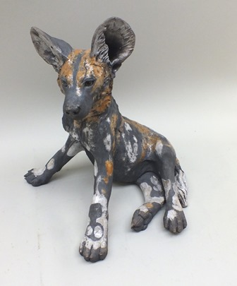 Nick Mackman A Raku-fired pottery sculpture of  Wild Dog Pup, seated, ears pricked, partial glazed in white and ochre patches, 39cm high