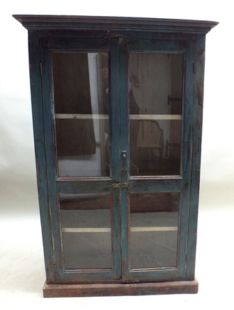 An Indian partially painted wood two door cupboard, fitted two glazed doors, revealing shelves, 88cm wide, 1.41m high