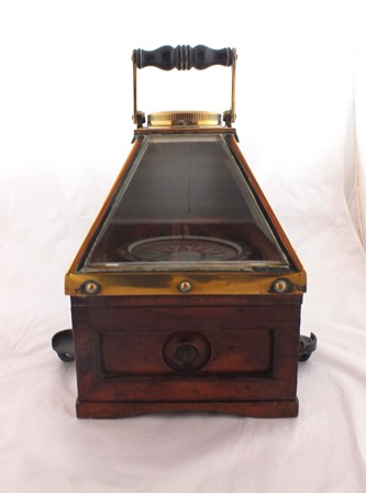 A Dents of London, improved liquid boat compass, circa 1900, glazed brass and polished mahogany binnacle, with swing carrying handle, opening base door, with original paper label, engraved to top Dent patent, no.766, patt.20 illustrated