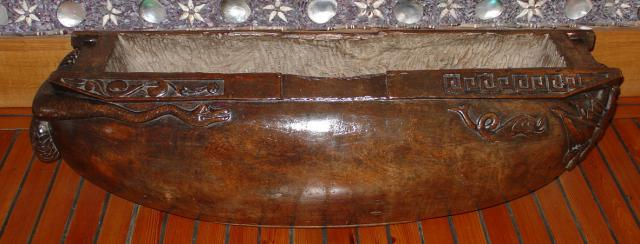 A 19th century Polynesian slit drum, hewn from one piece of hardwood, fashioned in boat form with scrolling serpent to the stern, dolphins and a shield cartouche to the prow, 1.34m wide, 40cm deep, 42cm high