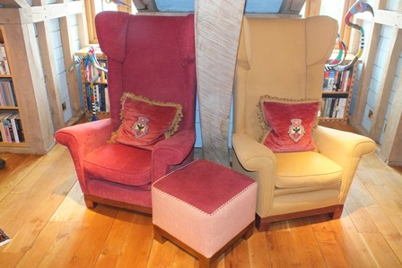 A pair of contemporary wing back easy chairs, having high backs and loose seat pads, one upholstered in red fabric, the other gold, together with a footstool and pair of scatter cushions, with embroidered spread eagle crest illustrated